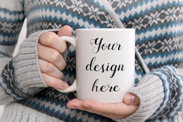 女性の手で白いコーヒーのマグカップのモックアップ