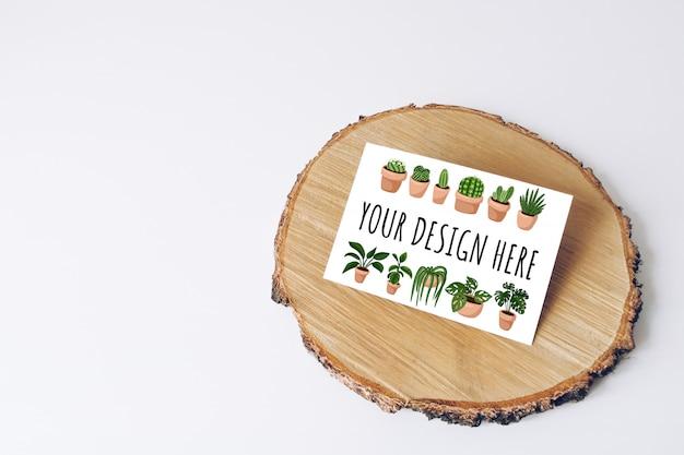 白いテーブルの上の木製のカットツリーセクションの水平のはがきのモックアップ。