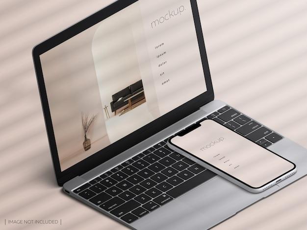アイソメトリック分離されたmacbookラップトップとスマートフォンデバイス画面のモックアップ