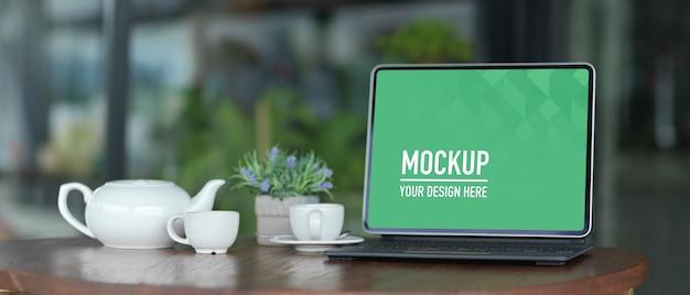 Макет экрана портативного компьютера с канцелярскими принадлежностями на белом столе