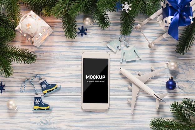クリスマスの装飾が施された画面のスマートフォンのモックアップ