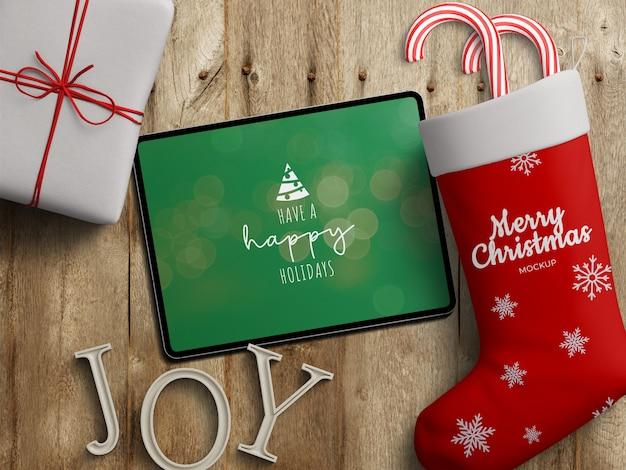 나무 테이블에 크리스마스 장식과 함께 태블릿 화면과 스타킹 양말의 모형