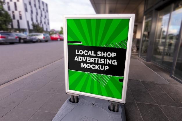 通りの街の屋外広告垂直ポスターのモックアップは、地元のお店でシルバーフレームに立つ