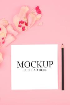鉛筆とピンクの花と白いノートのモックアップ