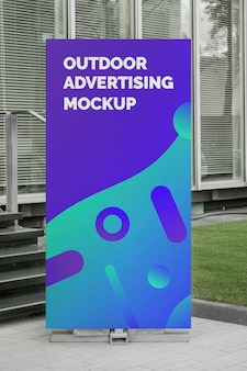 Mockup of outdoor advertising vertical poster rollup stand at the office entrance