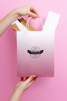 Макет пакета в руках на розовом пространстве