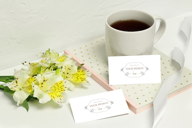 Mockup paper cards on white background with beautiful flowers, notes, ribbon and cup of coffee