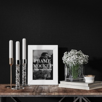 Mockup photo frame beside flowers and candles