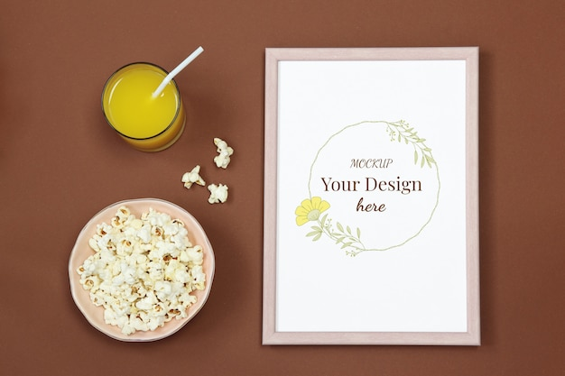 Mockup photo frame with glass of juice and popcorn on brown background
