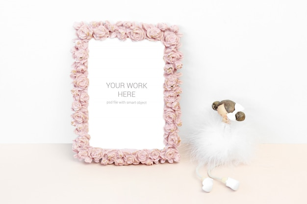 Mockup photo frame with pink rose flower and statuette