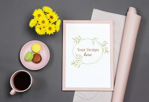 Mockup photo frame with yellow bouquet, cup of coffee and macaron on black background