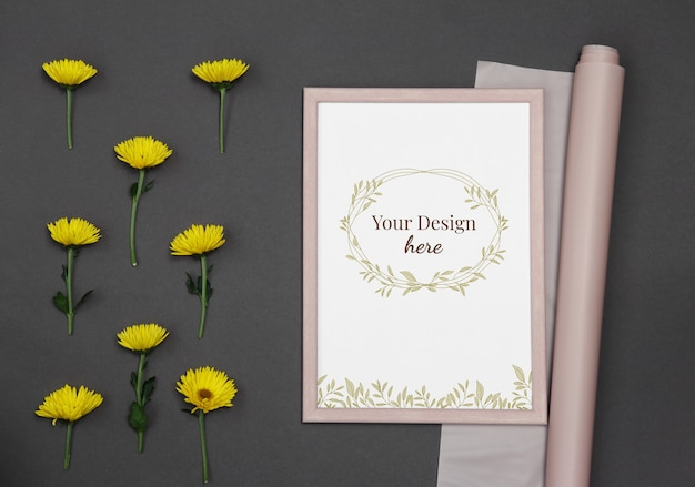 Mockup photo frame with yellow flowers and pink paper on dark background