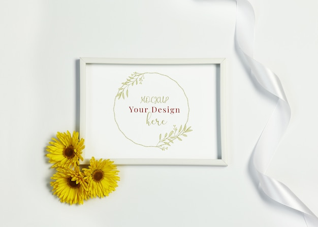 Mockup photo frame with yellow flowers and ribbon on white background
