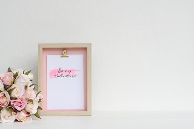 モックアップ額縁とピンクのバラ。コピースペースでバレンタインデーの背景概念。写真やテキスト用のスペースを備えたフォトフレームと花でモックアップ