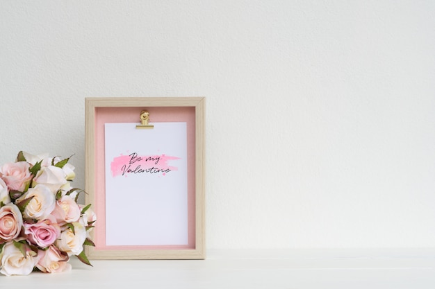 Mockup picture frame and pink roses. valentines day background concept with copy space. mock up with photo frame and flowers with space for your picture or text