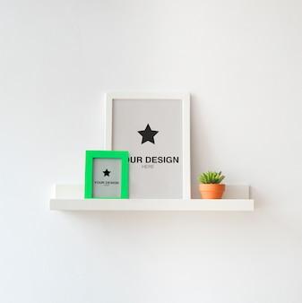 Макет рамы для картин (редактируемый цвет) на белой полке с растением