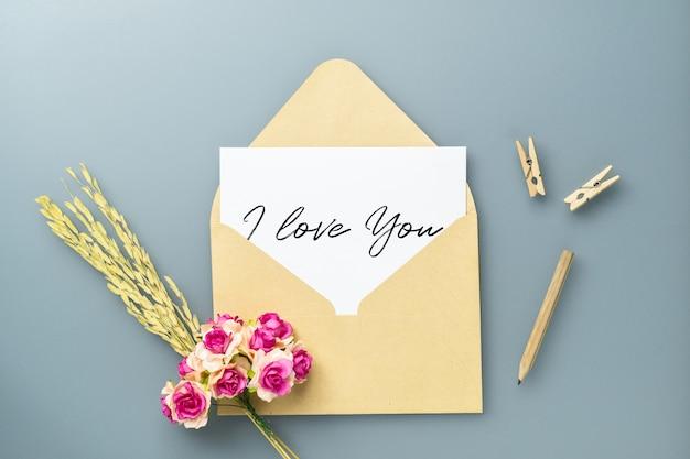이랑 엽서와 공예 장미 꽃과 회색 테이블에 봉투.