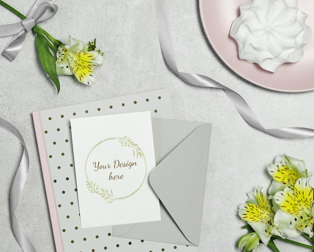 Mockup postcard on grey background with flowers, cake and ribbon