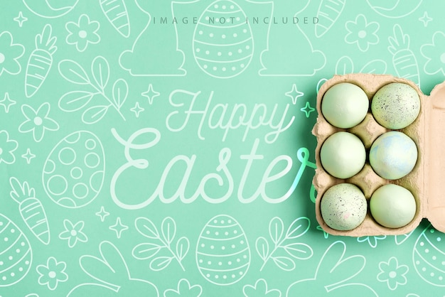Mockup postcard with paper container of painted green eggs on a green color surface,  happy easter concept.