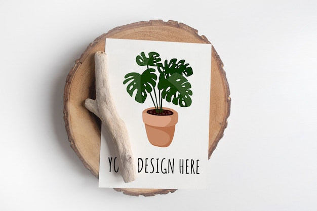 Mockup of postcard on wooden cut tree section on white table. boho design of postcard on white table