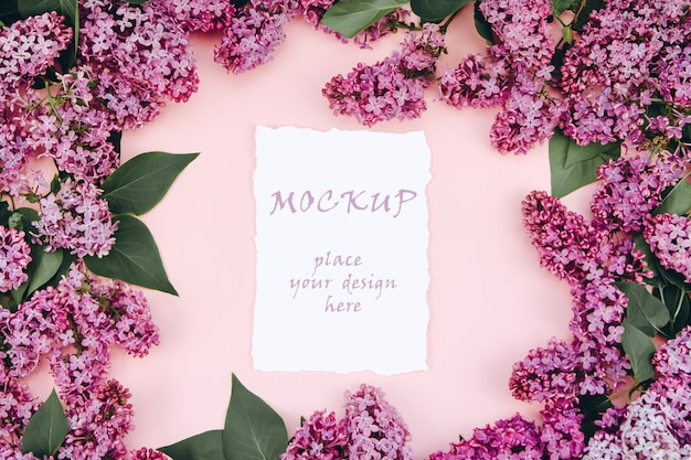 Макет открытки на розовом фоне с ветвями цветущей сирени