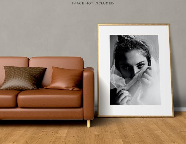 Рамка плаката макета в пустой деревянной раме, стоящей на современном интерьере гостиной.