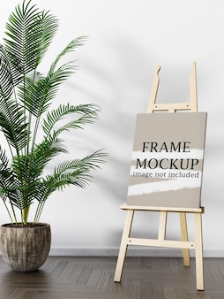 Mockup poster with easel beside plant