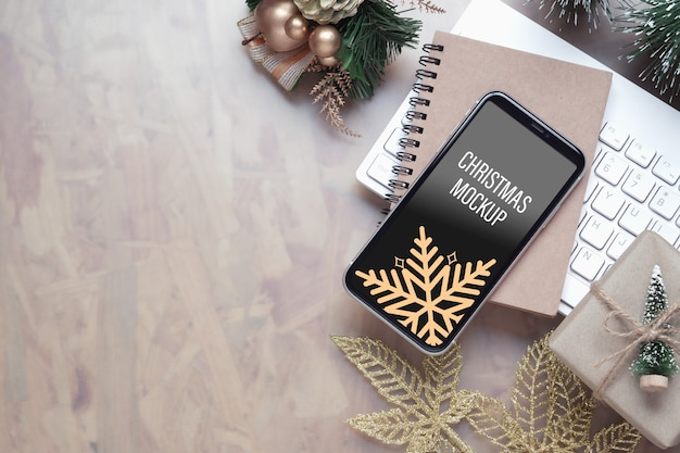クリスマスと新年の背景のためのホームオフィスの机の上のモックアップスマートフォン