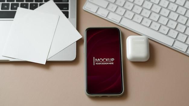 Макет смартфона на рабочем столе с канцелярскими принадлежностями в офисной комнате