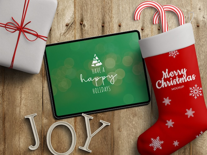Mockup of tablet screen and stocking sock with christmas decoration on wooden table
