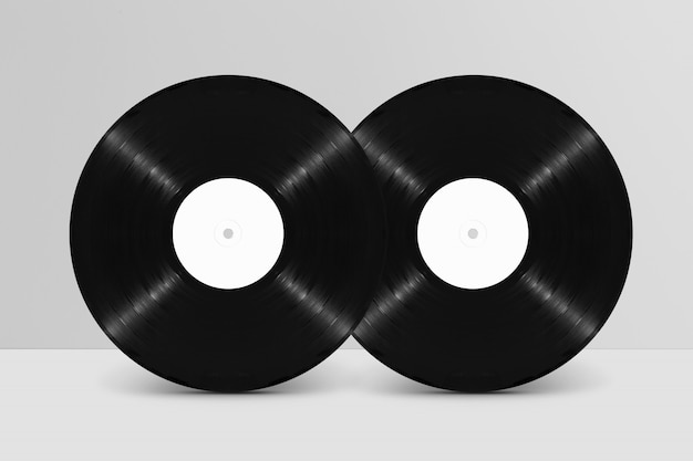 Mockup of two front view standing blank vinyl records against white wall