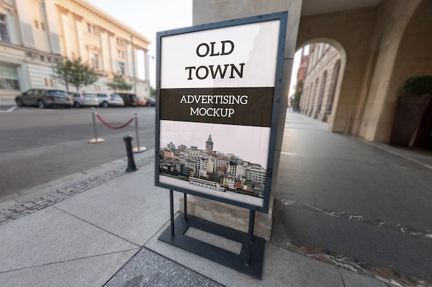 Mockup of vertical outdoor classic black metallic advertising frame stand on old town pavement