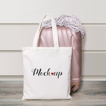 Mockup of a white cotton eco tote bag with travel suitcase