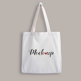 Mockup of a white cotton tote bag hanging on a wall