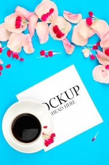 Mockup of white paper cup of coffee and pink flowers on a blue background
