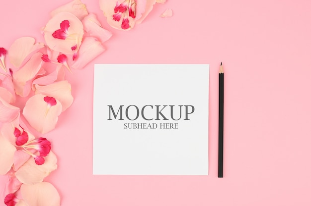 Mockup of white paper and pink flowers on a pink background