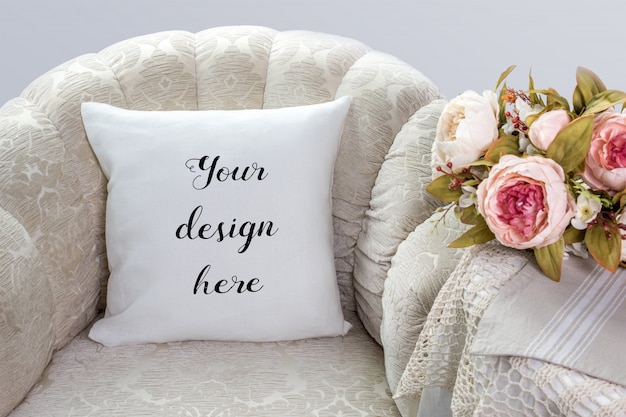 Mockup of white pillow, cushion on an armchair with flowers
