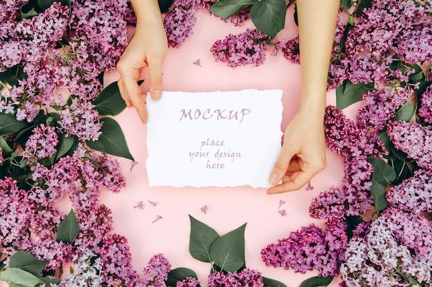 Макет с открыткой в женских руках на розовом фоне с цветущими ветвями сирени
