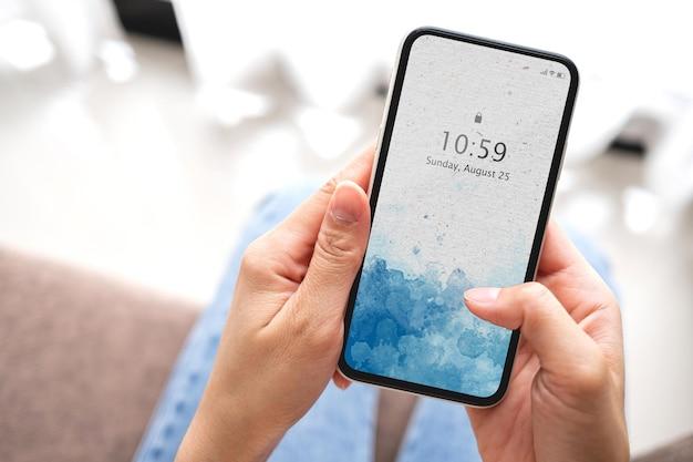 Рука женщины макета, держащая черный смартфон с пустым белым экраном на диване у себя дома. концепция бизнеса и технологий