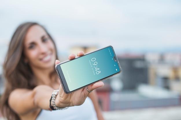 Женщина, держащая смартфон mockup