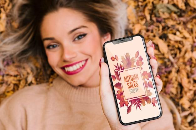 Модель показывает свой телефон и улыбается