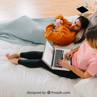 Modern couple with laptop in bed