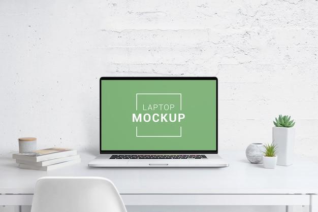 オフィスの机の上の現代のラップトップのモックアップ