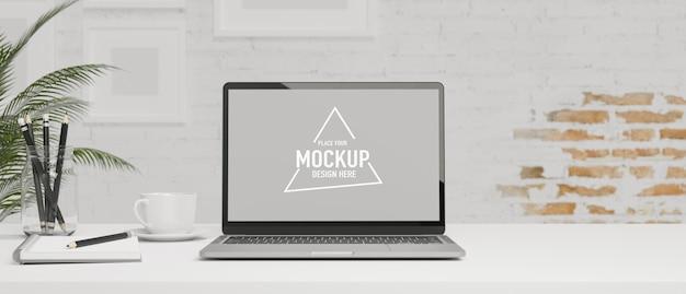 白いワークデスクの白いレンガの壁にキーボードの文房具を備えたモダンなワークスペースの空白の画面のタブレット