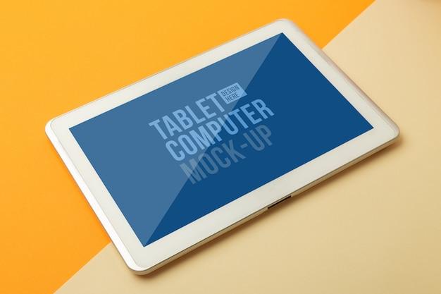 あなたのデザインのタブレットコンピューターのモックアップテンプレートを備えたモダンな作業スペース、オレンジ色のオフィステーブルデスク