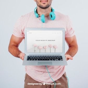 Modern young guy holding laptop's mock up