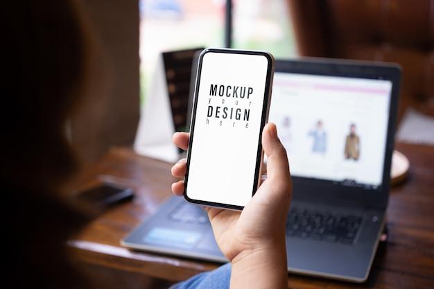 Mokcup мобильный телефон. персона держа и используя smartphone и компьтер-книжку нерезкости на деревянном столе в кафе.