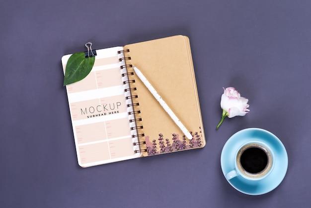 朝のコーヒーマグカップ、空のノートブック、暗いテーブル、鉛筆と白いトルコギキョウの花、居心地の良い朝食、トップビュー、コピースペース