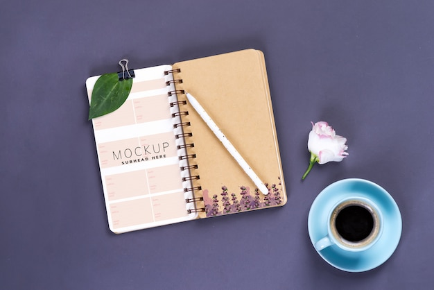 Morning coffee mug, empty notebook, pencil and white eustoma flower on dark table, cozy breakfast, top view, copy space