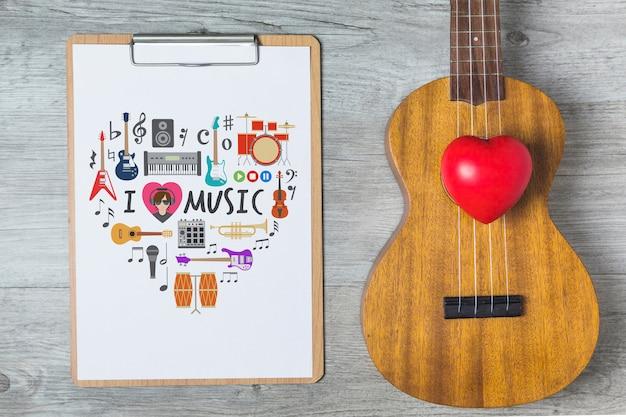 기타와 클립 보드가있는 음악 모형